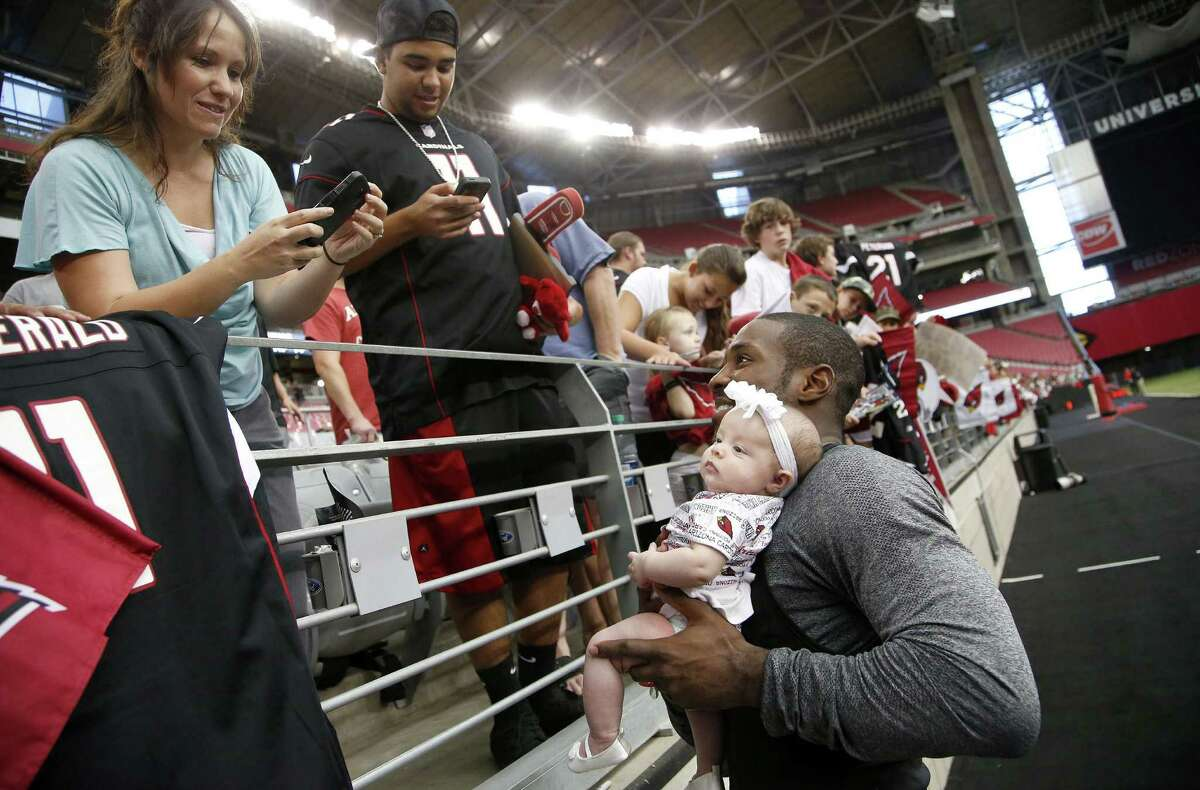 Arizona Cardinals' Patrick Peterson, right, poses for a picture with two-month-old Ariana Ortiz, as her mother Maria Ortiz, left, of Phoenix, snaps the photo with her phone after Cardinals NFL football training camp practice on Wednesday, July 30, 2014, in Glendale, Ariz. (AP Photo/Ross D. Franklin)
