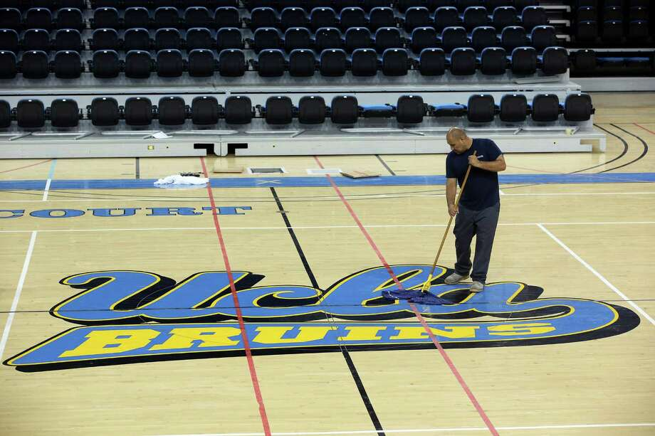 Worker Ruben Monter mops up the floor at Pauley Pavillion Wednesday July 30, 2014 in Los Angeles. A ruptured 93-year-old water main on Tuesday left the UCLA campus awash in 8 million gallons of water in the middle of California's worst drought in decades, stranding people in parking garages and flooding the school's storied basketball court less than two years after a major renovation.  (AP Photo/ Nick Ut) ORG XMIT: LA103 Photo: Nick UT / AP