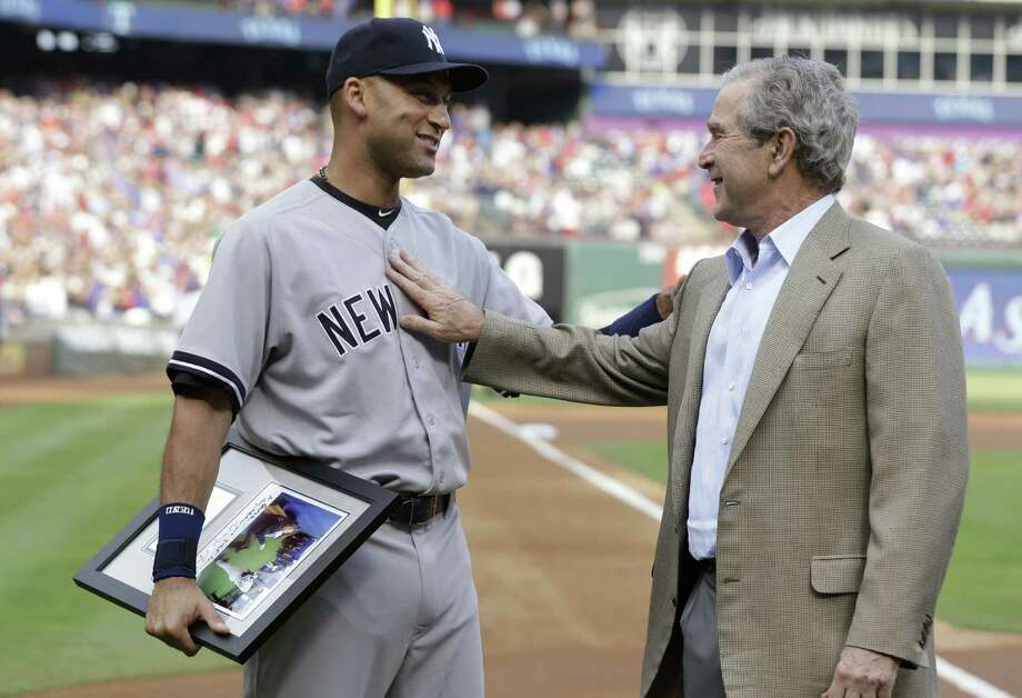 Derek Jeter and former President George W. Bush greet each other during a ceremony honoring Jeter's final game in Arlington. Jeter went 0 for 4 in Texas' victory. Photo: L.M. Otero / Associated Press / AP