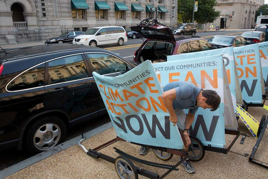An activist sets up a sign for a rally at the Environmental Protection Agency in Washington. Religious groups came to show support for a new EPA rule limiting power plant emissions. Photo: Stephen Crowley, New York Times