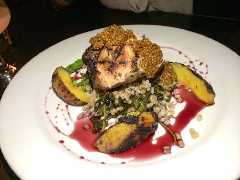 Pork is blanketed in mustard seed with grilled peaches, farro, spigarello, asparagus and red wine jus ($25.50).