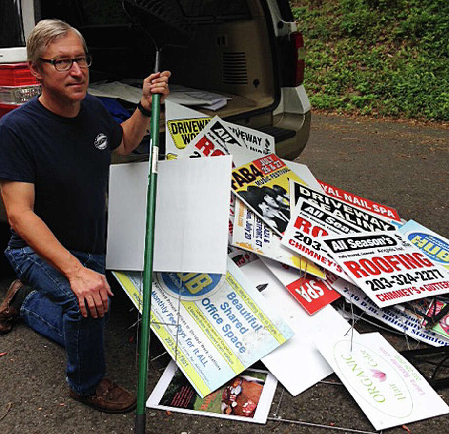 "Planning and Zoning Commission member Alfred Gratix Jr., who with P&Z Chairman Chip Stephens is one of the ""De-Signers,"" with a haul of illegally posted roadside signs the men recently took down. Photo: Contributed Photo / Westport News"