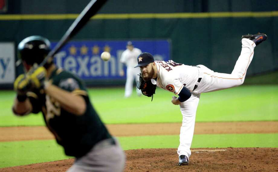 Houston Astros starting pitcher Dallas Keuchel, right, throws to Oakland Athletics' Josh Reddick, left, during the eighth inning of a baseball game Wednesday, July 30, 2014, in Houston. (AP Photo/David J. Phillip) Photo: David J. Phillip, Associated Press / AP