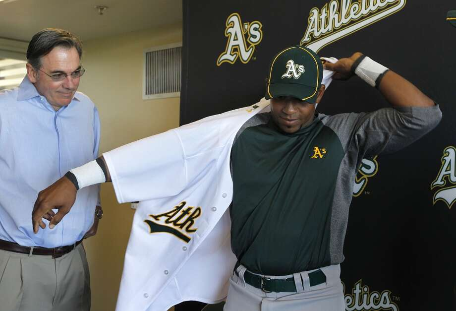 General Manager Billy Beane watches his newest player, Yoenis Cespedes, don a uniform after his arrival at the Oakland A's camp in Phoenix, Ariz. on Sunday, March 4, 2012. Cespedes, who defected from Cuba,  signed a four-year contract with Oakland. Photo: Paul Chinn, The Chronicle