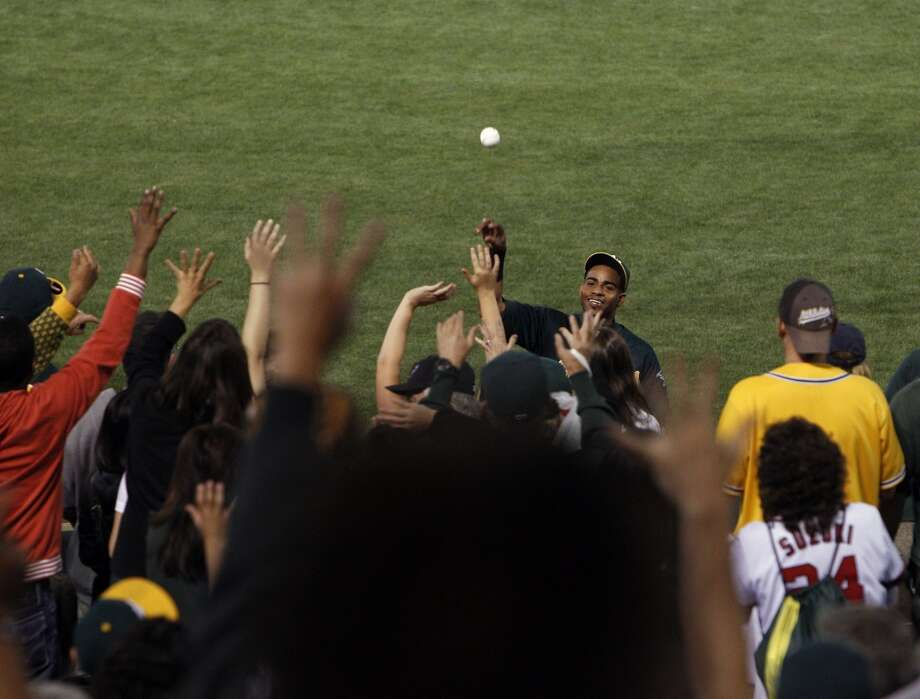 Yoenis Cespedes, of the Oakland Athletics, tries to throw a ball to his family after the game against the Chicago White Sox on Friday, May 31, 2013, in Oakland, Calif. Photo: Carlos Avila Gonzalez, The Chronicle