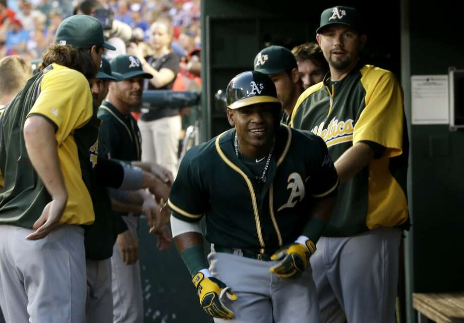 Oakland Athletics' Yoenis Cespedes, center, is congratulated in the dugout after his solo home run off of Texas Rangers starting pitcher Nick Tepesch in the sixth inning of a baseball game, Saturday, July 26, 2014, in Arlington, Texas. Photo: Tony Gutierrez, Associated Press