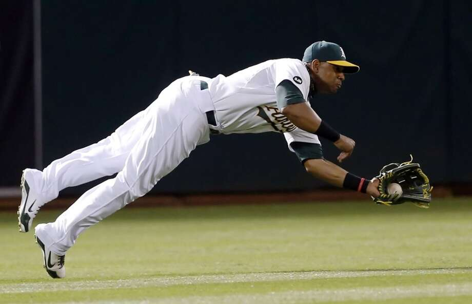 Yoenis Cespedes makes a diving catch on a ball hit by Prince Fielder in the top of the seventh inning. The Oakland Athletics played the Detroit Tigers in game 3 of the ALDS at O.co Coliseum in Oakland, Calif., on Tuesday, October 9, 2012. Photo: Beck Diefenbach, Special To The Chronicle