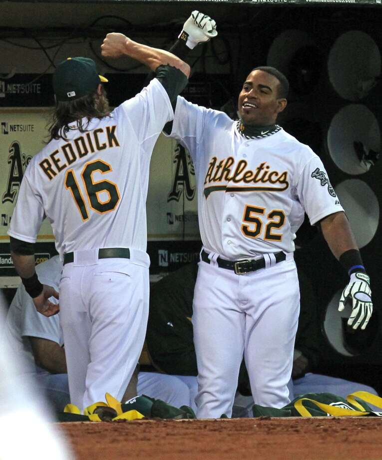 Oakland Athletics Josh Reddick (16) celebrates with Yoenis Cespedes (52) after he hit a solo home run in the second inning during their MLB baseball game against the Seattle Mariners Tuesday, April 2, 2013 in Oakland, Calif. Photo: Lance Iversen, The Chronicle