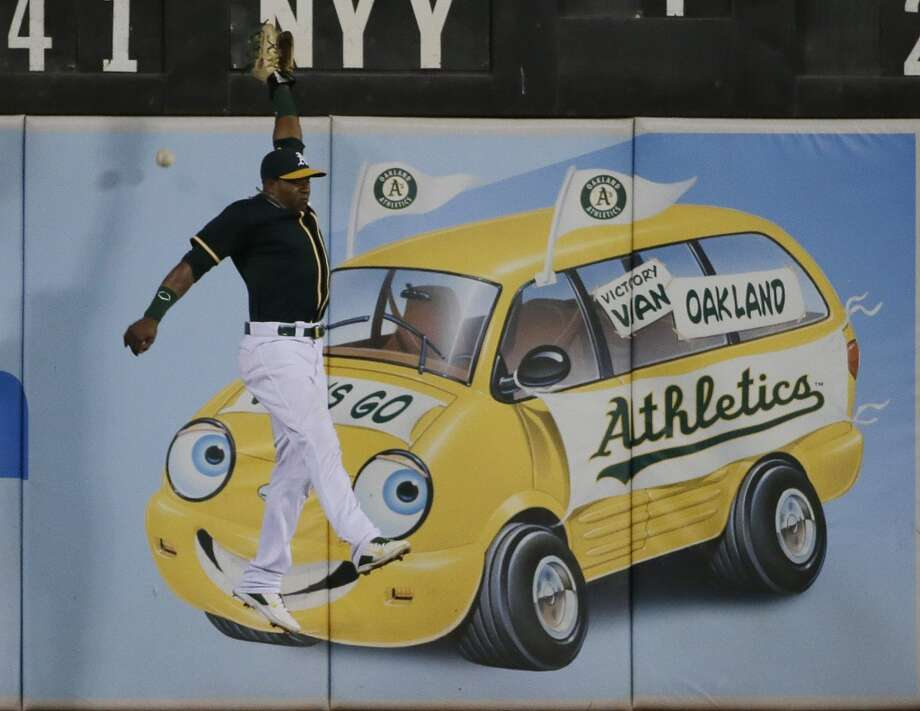 Oakland Athletics left fielder Yoenis Cespedes leaps but can't catch a fly ball by Houston Astros' Jon Singleton during the sixth inning of a baseball game on Wednesday, July 23, 2014, in Oakland, Calif.  Singleton got a double on the play. Photo: Associated Press