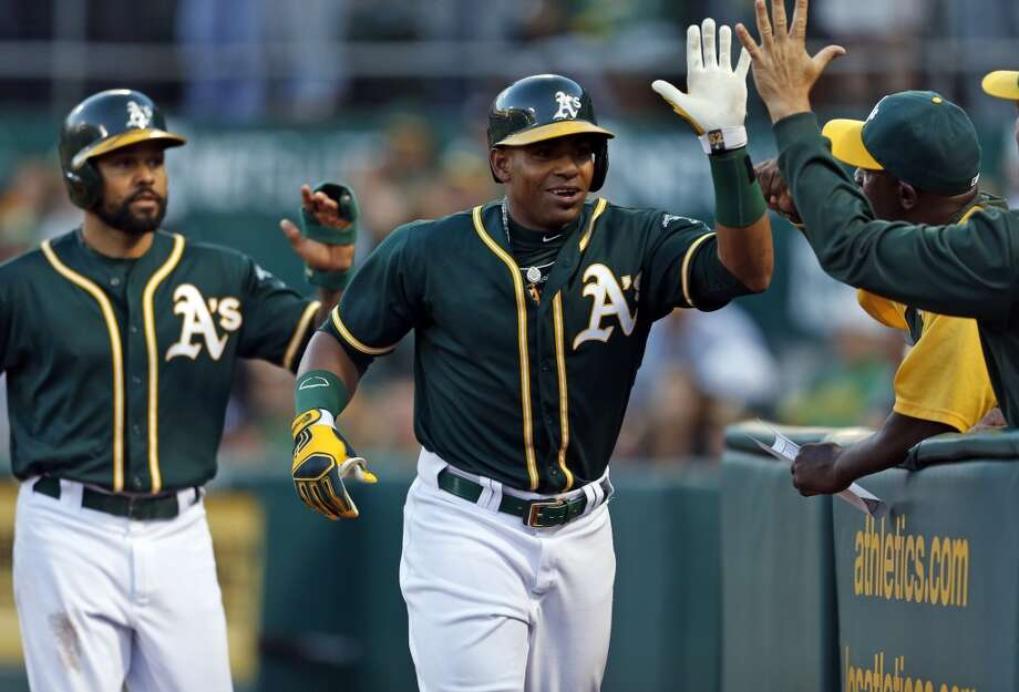 Oakland Athletics' Yoenis Cespedes and Coco Crisp celebrate Cespedes' 3-run home run in 2nd inning against Houston Astros' Brad Peacock during MLB game at O.co Coliseum in Oakland, Calif. on Wednesday, July 23, 2014. Photo: Scott Strazzante, The Chronicle