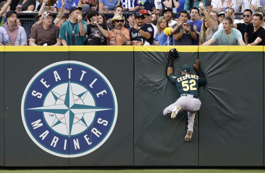 Oakland Athletics center fielder Yoenis Cespedes crashes into the pad after leaping at the wall for a fly ball from Seattle Mariners' Kyle Seager in the sixth inning of a baseball game Saturday, May 11, 2013, in Seattle. Cespedes made the catch. Photo: Elaine Thompson, Associated Press