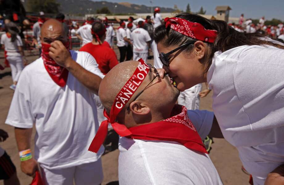 Gilberto Martinez gets a kiss from Brigette Arelis, both from Pittsburgh, moments before The Great Bull Run on Saturday July 26, 2014, at the Alameda County Fairgrounds in Pleasanton, Calif. Photo: Michael Macor, The Chronicle