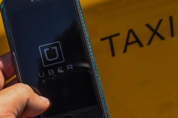 In this photo illustration, the new smart phone app 'Uber' logo is displayed on a mobile phone next to a taxi on July 1, 2014 in Barcelona, Spain.(Photo Illustration by David Ramos/Getty Images)