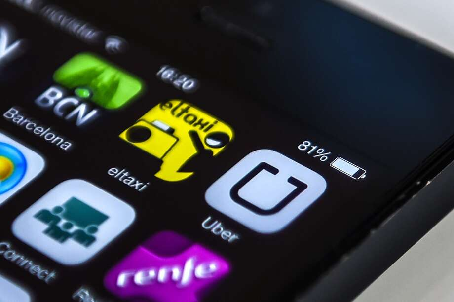In this photo illustration, logos of 'Uber',  a Barcelona taxi and Barcelona City guide apps are seen in a smart phone on July 1, 2014 in Barcelona, Spain. (Photo Illustration by David Ramos/Getty Images) Photo: David Ramos, Getty Images