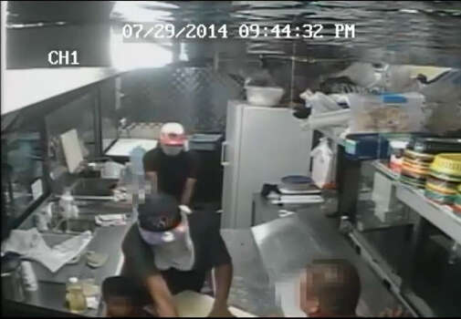 Two masked gunmen held up at Tacos Poncho's located at 10303 Airline Drive in Harris County, Texas on Tuesday, July 29, 2014. In this security camera footage of the aggravated robbery, they can be seen entering through the door of the taco truck, pointing their guns at the subjects inside, striking the man in orange, then robbing both the cash box and stealing the individual employees' wallets. Another employee was shot in the arm during the incident, which was not caught by the camera. | Harris County Sheriff's Office Photo: Harris County Sheriff's Office