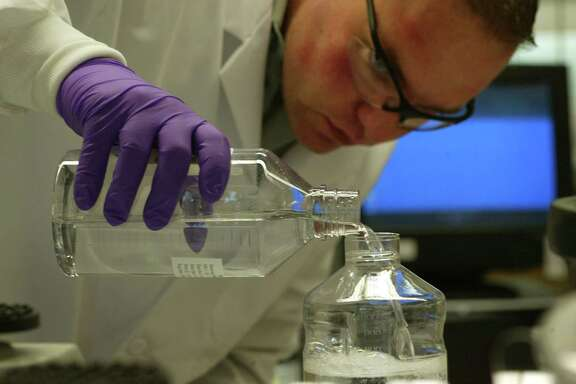 NATICK, MA - MAY 3: Globe 100 - #1 Boston Scientific Corp  - In the cell biology lab, associate scientist Jon Robbins prepares a solution to separate and identify an individual protein. (Photo by Pat Greenhouse/The Boston Globe via Getty Images)