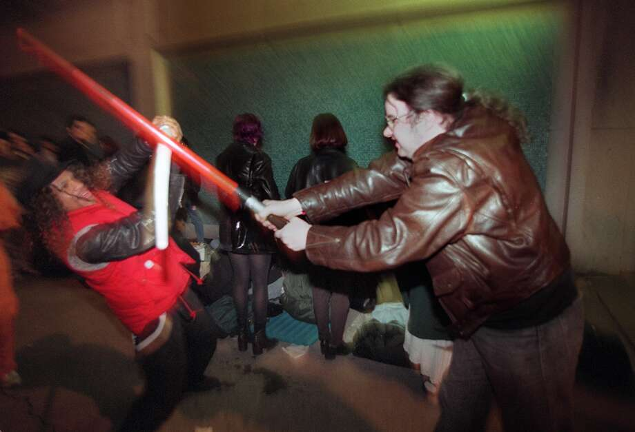 """Die hard"" Star Wars fans Mel Carter, 27, and Tony Case, 28, go at it with light sabers while waiting for the 7:15 showing at the Cinerama in downtown Seattle of the new edition of the science fiction classic in 1997. Photo: PAUL JOSEPH BROWN, P-I File"