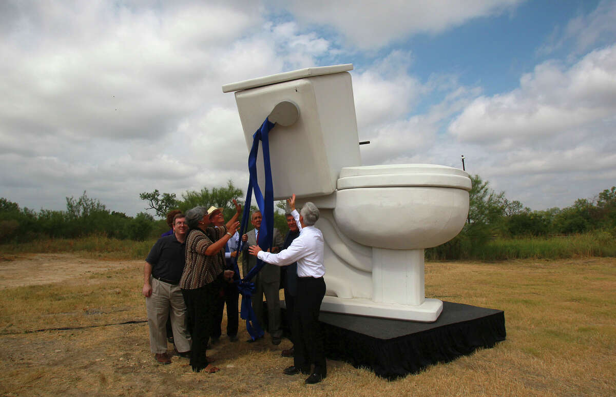 San Antonio Water System officials and others attempt to flush a giant mock toilet Thursday July 31, 2014 during a press conference to announce the completion of the Southwest Bexar Sewer Pipeline project. The project is a 32-mile pipeline that links parts of far west and south San Antonio to the Dos Rios Water Recycing Center. The mock toilet fell sideways when the handle was pulled and nobody was injured. The event took place on the side of Interstate 35 by the Medina River.