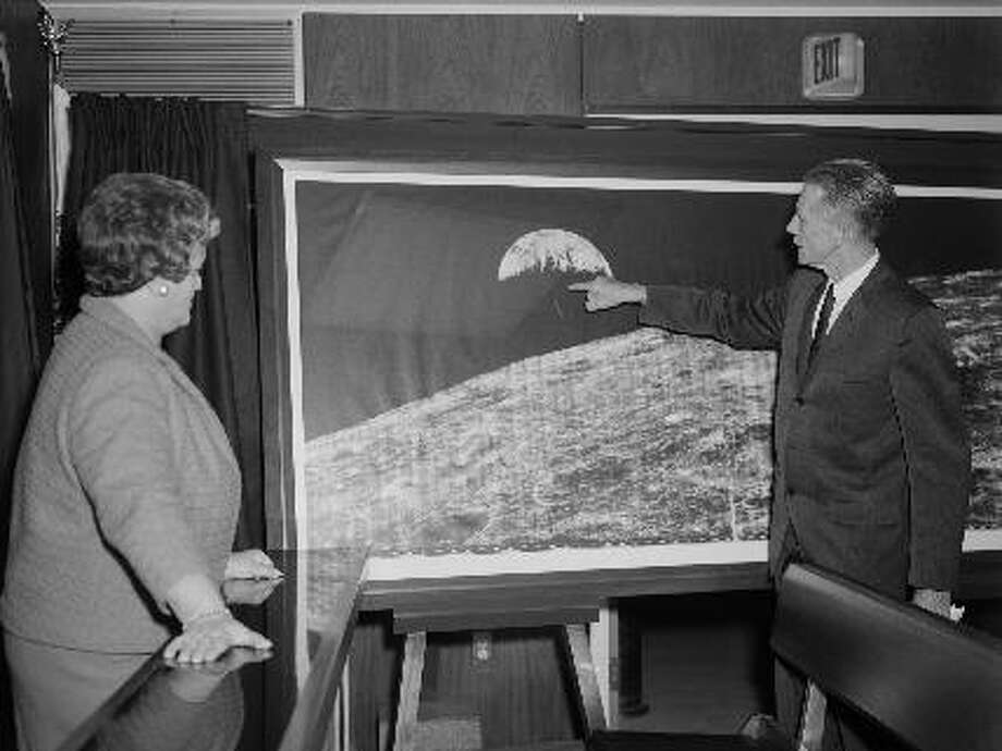 """: Former Langley Center Director Floyd Thompson shows Ann Kilgore the """"picture of the century."""" This was the first picture of the earth taken from space on Aug. 23, 1966. (NASA) Photo: NASA Lunar Orbiter Image Recovery Project"""