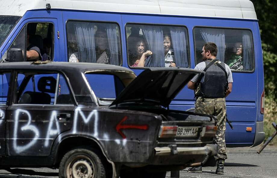 Passengers look through the windows of a minibus as a Ukrainian soldier stands guard at a check-point in the Donetsk region. Photo: Bulent Kilic, AFP/Getty Images