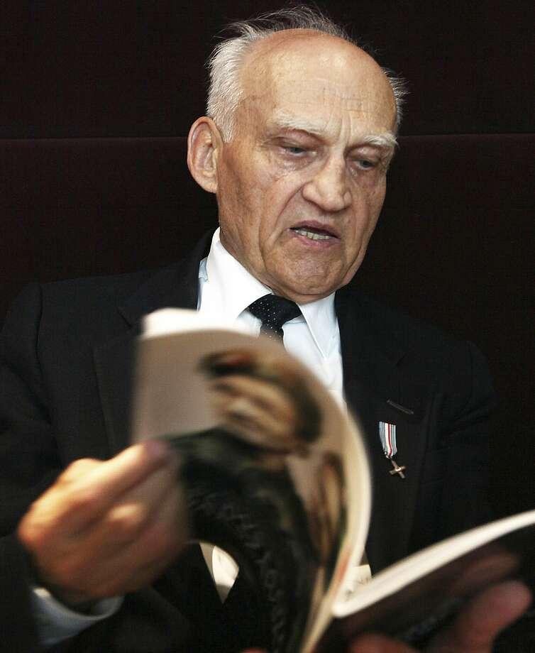 Kazimierz Mikos holds a book about the uprising. Photo: Czarek Sokolowski, Associated Press