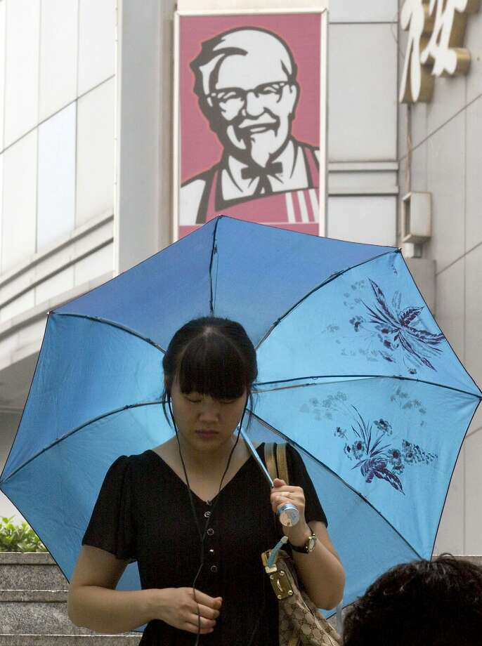 A woman walks past a logo for KFC outside a mall in Beijing, China, Thursday, July 31, 2014. Already China's biggest restaurant operator with 4,600 outlets, KFC the Louisville, Kentucky-based chain is reeling after a Chinese supplier was accused of selling expired beef and chicken to it, McDonald's and possibly other restaurant chains. Just 18 months earlier, KFC's sales plunged in China after a supplier violated rules on drug use in chickens.(AP Photo/Ng Han Guan) Photo: Ng Han Guan, Associated Press