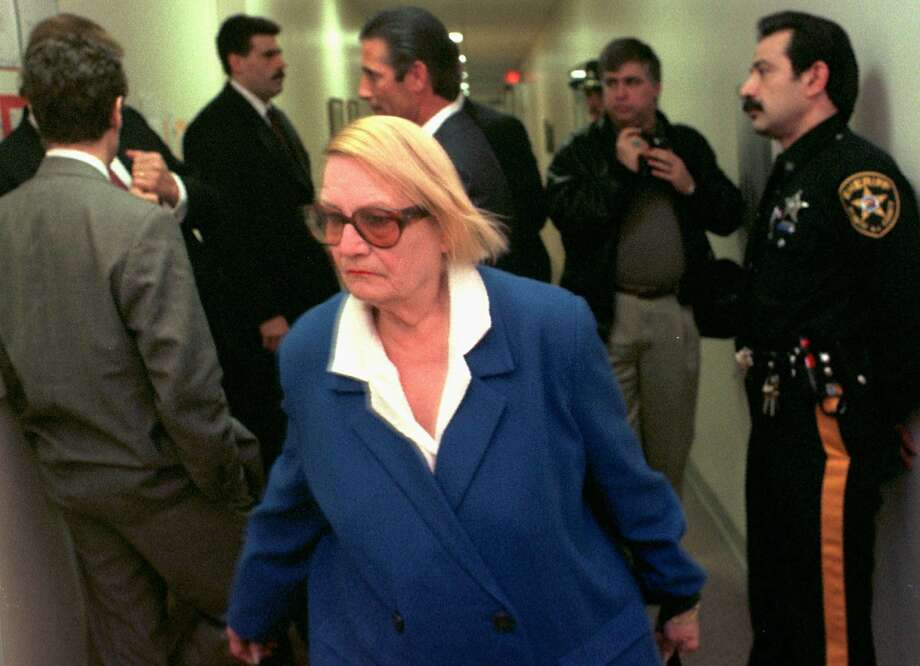 FILE - In this Thursday Feb. 13, 1997, file photo, Vera Coking walks past Donald Trump, partially obscured against wall at left, in a courtroom hallway at Atlantic County Superior Court in Atlantic City, N.J. Coking, who became a folk hero for resisting decades-long efforts by big-name developers like Trump to displace her Atlantic City boardinghouse, is now 91 and, at last, ready to sell. Coking's boardinghouse goes up for auction Thursday, July 31, 2014, for a $199,000 starting bid. (AP Photo/Allen Oliver, File) Photo: Allen Oliver, Associated Press