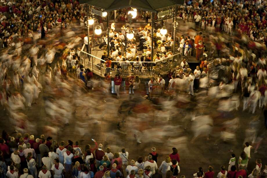 "Round and round we go: Revelers circle a band stage in the Plaza de Los Fueros Square during ""La Revoltosa"" dance in honor 