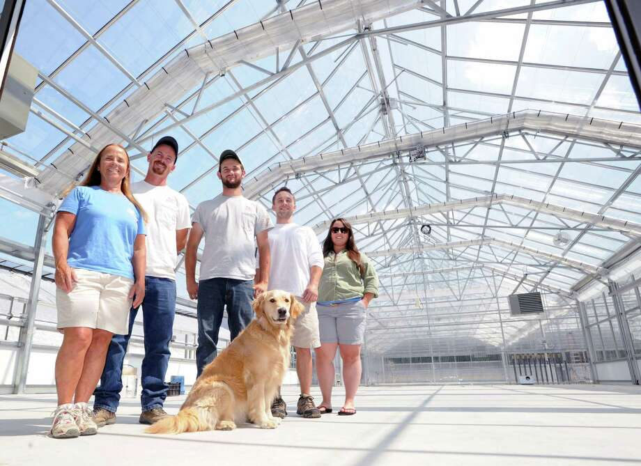 Sam Bridge Nursery & Greenhouses family members from left, Mary Jo Palmer, her son, Rich Palmer, Nick Bridge, Sam Bridge IV and Maggie Bridge and dog, Shea, inside their new 26,000 square foot facility that will serve multiple functions for their family-run business that is located on North Street in Greenwich, Conn., Thursday, July 31, 2014. Photo: Bob Luckey / Greenwich Time