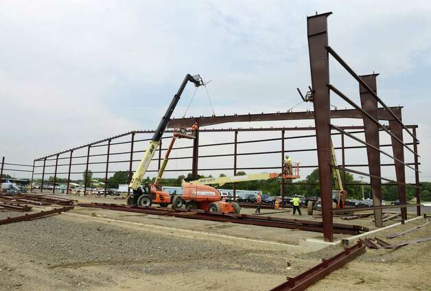Workers with Plank Construction form the steel superstructure for a new aircraft hangar at Richmor Aviation Thursday, July 31, 2014, at Schenectady County Airport in Scotia, N.Y. Cost for the 20,000 square foot hangar is billed at $1.2 million. It will double their current hangar capacity.  Richmor sited growth in the areaa€™s high tech businesses as impetus to build the new structure. (Will Waldron/Times Union) Photo: WW / 00027997A