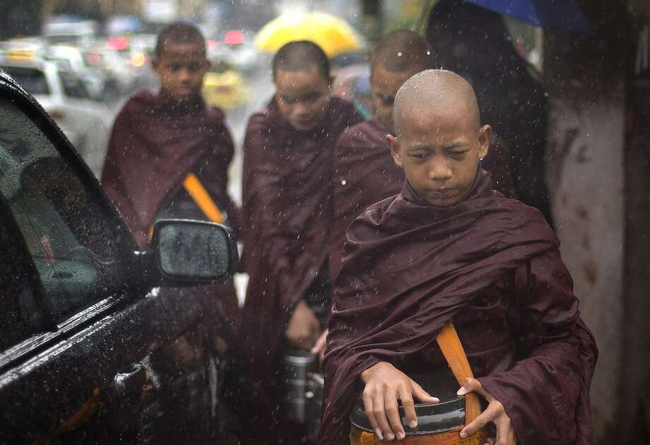 Wet apprentices: Novice Buddhist monks prepare to collect alms in the rain in a street in Yangon, Myanmar. They are forbidden from wearing footwear or using umbrellas despite the weather. Photo: Gemunu Amarasinghe, Associated Press