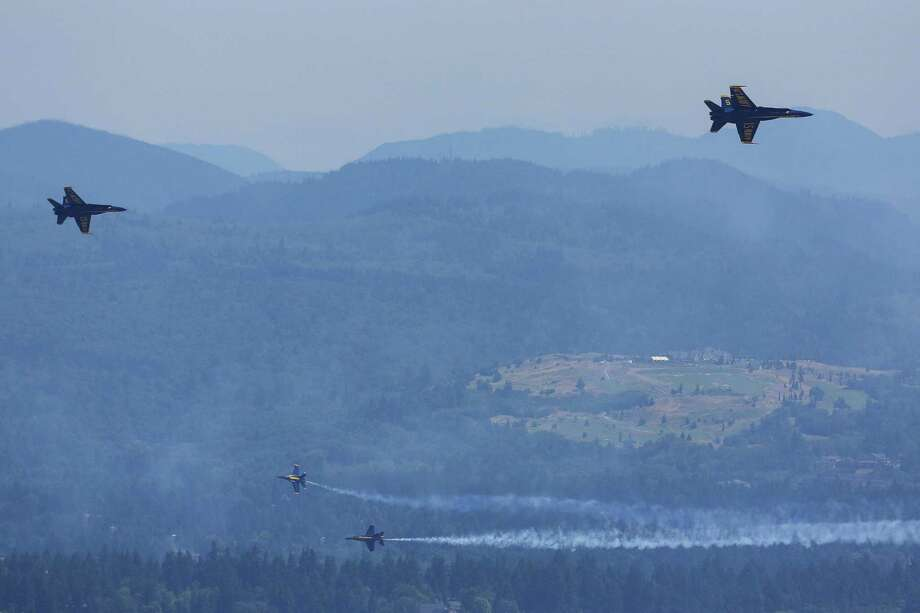 As seen from the Columbia Skyview Observatory, the U.S. Navy Blue Angels perform aerial maneuvers and formations over Seattle and Lake Washington as part of a practice session on Thursday July 31, 2014. The practice caused the closing of the Interstate 90 Bridge for parts of the morning and afternoon. Photo: JOSHUA BESSEX, SEATTLEPI.COM / SEATTLEPI.COM