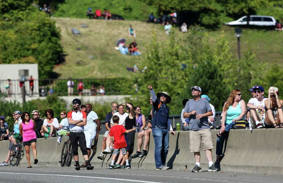 People watch from the Interstate 90 Bridge as the U.S. Navy Blue Angels perform aerial maneuvers and formations over Seattle and Lake Washington as part of a practice session on Thursday July 31, 2014. The practice caused the closing of the I-90 Bridge for parts of the morning and afternoon. Photo: JOSHUA BESSEX, SEATTLEPI.COM / SEATTLEPI.COM