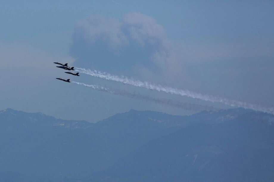 As seen from the Columbia Skyview Observatory, the U.S. Navy Blue Angels pass by a smoke plume from wildfires in eastern Washington while performing aerial maneuvers and formations over Seattle and Lake Washington as part of a practice session on Thursday July 31, 2014. The practice caused the closing of the Interstate 90 Bridge for parts of the morning and afternoon. Photo: JOSHUA BESSEX, SEATTLEPI.COM / SEATTLEPI.COM