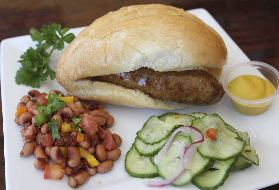 The bright and tangy flavors of black-eyed pea salad and German cucumber salad complement Hungarian sausage. Beer-brat mustard accompanies. Photo: Photos By Tom Reel / San Antonio Express-News