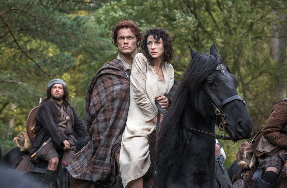 Claire Randall (Caitriona Balfe), a married nurse from 1945, is swept back to 1743 and into the protective arms of Jamie Fraser (Sam Heughan), who's traveling with a band of warriors that includes opportunist Rupert MacKenzie (Grant O'Rourke, left). Photo: Sony Pictures Television / © 2014 Sony Pictures Television Inc. All Rights Reserved.