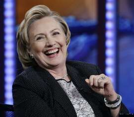 "In this July 15, 2014, photo, former U.S. Secretary of State Hillary Rodham Clinton reacts to host Jon Stewart during a taping of ""The Daily Show with Jon Stewart,"" in New York. As Clinton promotes her book, liberals in the Democratic party are elbowing into the 2016 presidential conversation while pitching populist messages on the economy and immigration.  (AP Photo/Frank Franklin II)"