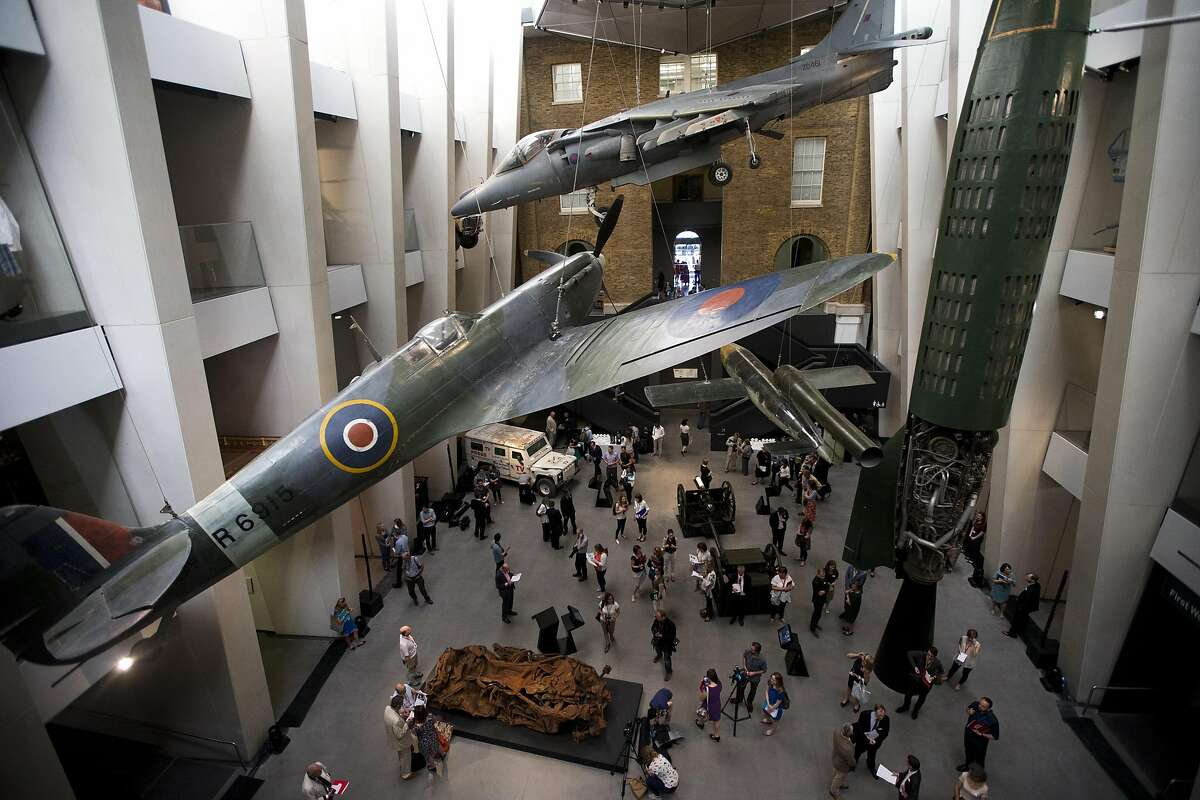 Members of the media gather during a press launch in the newly transformed atrium after major redevelopment works at the Imperial War Museum in London, Wednesday, July 16, 2014. The museum reopens Saturday after a six-month closure for a 40 million pound ($70 million) renovation timed to mark the centenary of World War I. The museum was founded in 1917, as the war still raged, to preserve the stories of those who were fighting and dying. It retains that goal, as well its archaic name, relic of a long-gone British Empire. (AP Photo/Matt Dunham)
