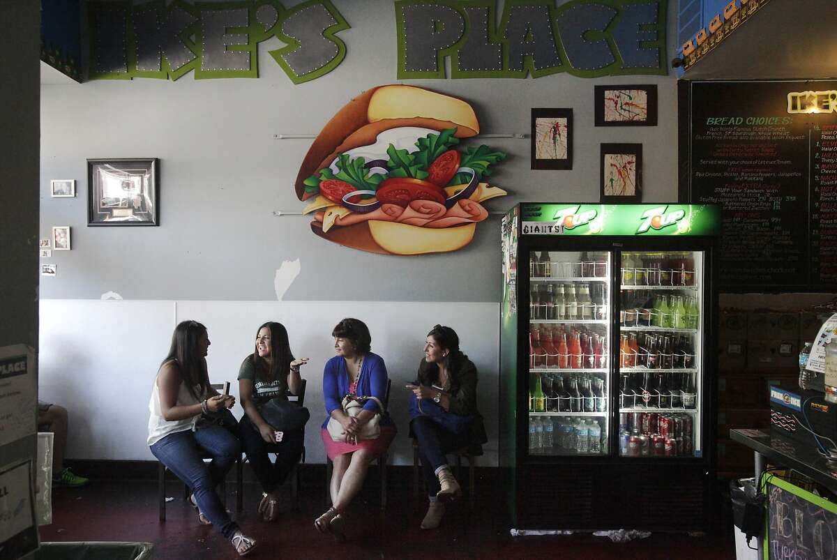Customers, from left, Laura, Celia, Maria and Adriana Rosas wait for their sandwiches at Ike's Place in the Castro July 30, 2014 in San Francisco, Calif. The sandwich chain has over 6,000 reviews on Yelp with an average of four and a half stars rating.