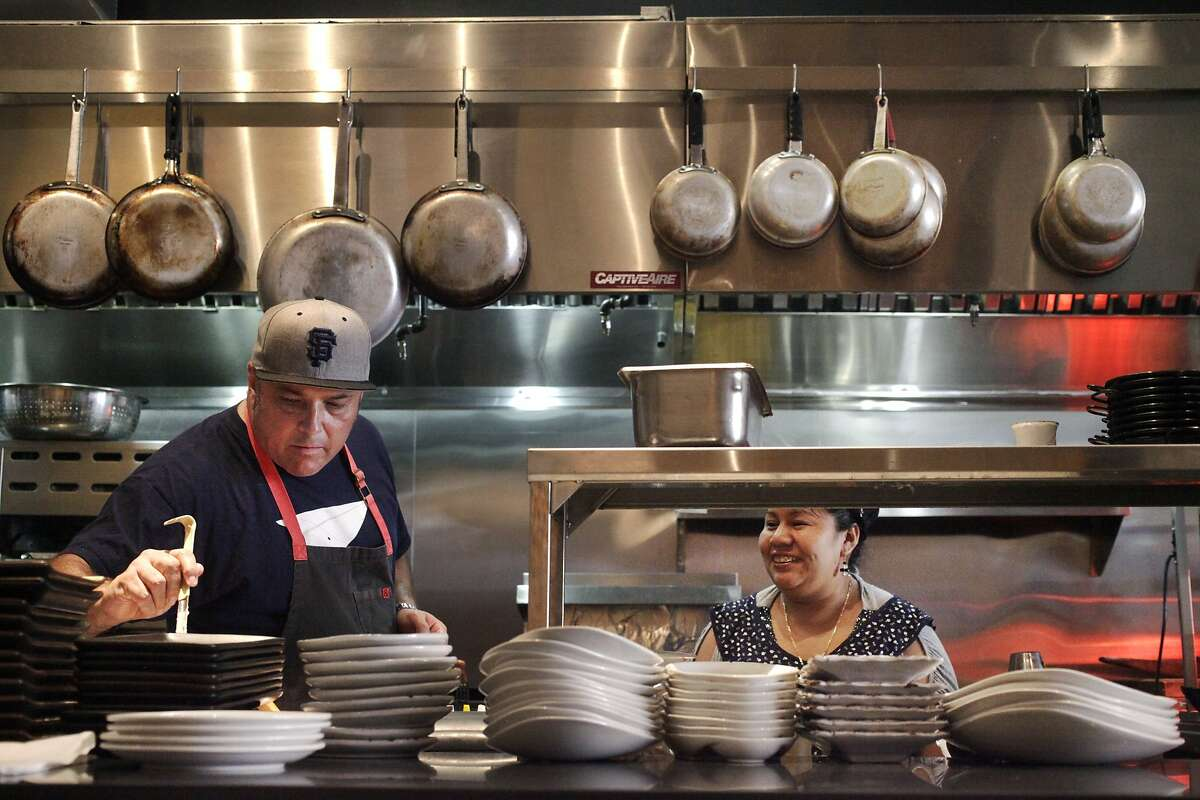 Chef Jorge Martinez takes a sample of a sauce while talking with Ruth Palo, line cook and tortilla-maker, as he works on setting up the line for the evening in the kitchen at Lolo July 30, 2014 in San Francisco, Calif. Lolo is a restaurant in the Mission featuring