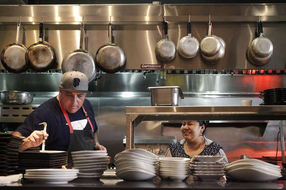 "Chef Jorge Martinez takes a sample of a sauce while talking with Ruth Palo, line cook and tortilla-maker, as he works on setting up the line for the evening in the kitchen at Lolo July 30, 2014 in San Francisco, Calif. Lolo is a restaurant in the Mission featuring ""Jaliscan-Californian inspired cuisine""."