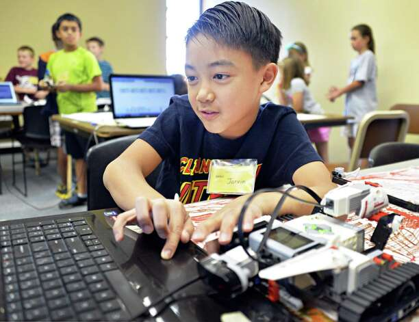 Nine-year-old Jarvin Dejesus of Niskayuna programs a Lego robot to navigate an obstacle course during a miSci summer class Thursday, July 31, 2014, in Schenectady, N.Y.  (John Carl D'Annibale / Times Union) Photo: John Carl D'Annibale / 00028004A