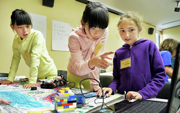 Twin sisters, Karen, left, and Kitty Ma, 10, of Albany, along with Elizabeth Jackson, 9, right, of Rotterdam program a Lego robot to navigate an obstacle course during a miSci summer class Thursday, July 31, 2014, in Schenectady, N.Y.  (John Carl D'Annibale / Times Union) Photo: John Carl D'Annibale / 00028004A
