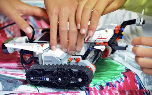 Children work with Lego robots during a miSci summer class Thursday, July 31, 2014, in Schenectady, NY. They programed them to navigate an obstacle course.  (John Carl D'Annibale / Times Union) Photo: John Carl D'Annibale / 00028004A