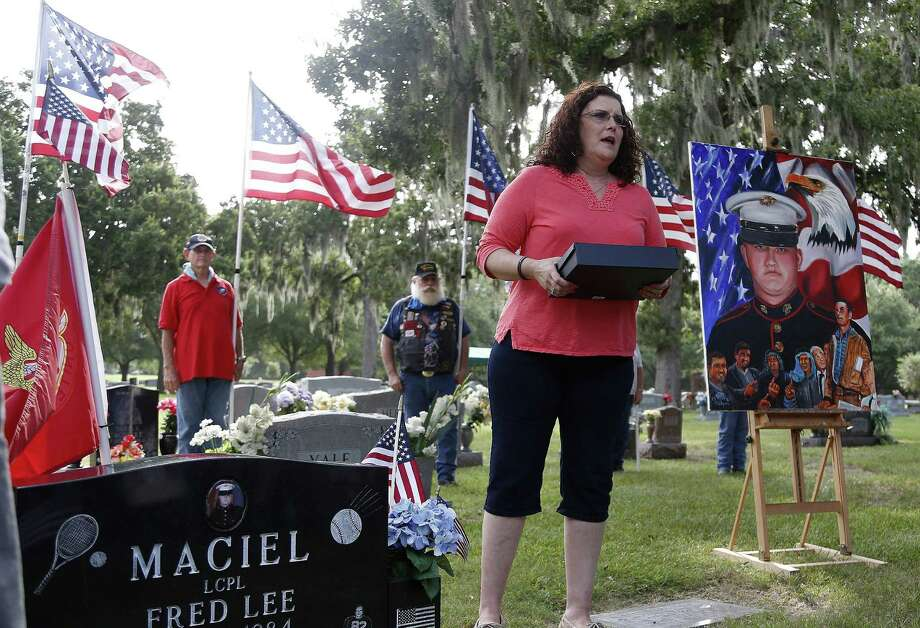 At Calvary Hill Cemetery in Houston, Lanie Brown prepares to hand over a tribute flag to Patsy Maciel, mother of Fred Maciel, who died in a helicopter crash in Iraq almost 10 years ago. Photo: Photos By Karen Warren / Houston Chronicle / © 2014 Houston Chronicle