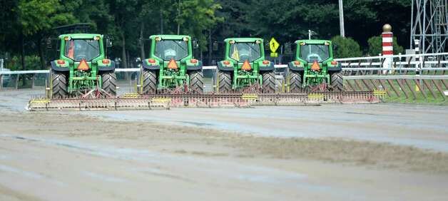 Tractors smooth the track surface to remove some of the moisture after heavy rains turned the track to slop Thursday afternoon July 31, 2014 at the Saratoga Race Course in Saratoga Springs, New York.    (Skip Dickstein / Times Union) Photo: SKIP DICKSTEIN