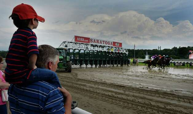 Trainer Bruce Brown breaks in his four year old son Nicholas as they watch the fourth race Thursday afternoon July 31, 2014 at the Saratoga Race Course in Saratoga Springs, New York.    (Skip Dickstein / Times Union) Photo: SKIP DICKSTEIN