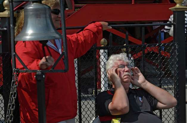 Photographer Dave Harmon holds his ears as the traditional bell is rung in the winner's circle Thursday afternoon July 31, 2014 at the Saratoga Race Course in Saratoga Springs, New York.    (Skip Dickstein / Times Union) Photo: SKIP DICKSTEIN