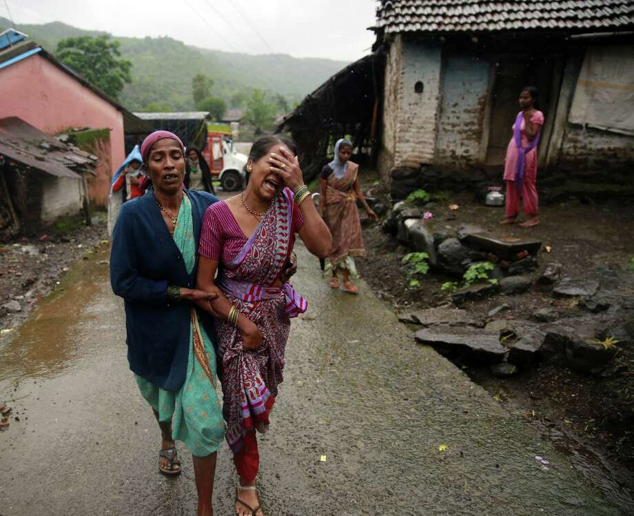 Women wail after seeing the body of a relative who was buried by the landslide Wednesday in the village of Malin. Two days of rain fell in western India leading up to the disaster. Photo: Rafiq Maqbool / Associated Press / AP