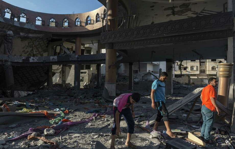 Palestinians examine the interior of a destroyed mosque in Gaza City. Israel continued attacks Thursday, killing at least 56 Palestinians, Gaza health officials said. Photo: Sergey Ponomarev / New York Times / NYTNS